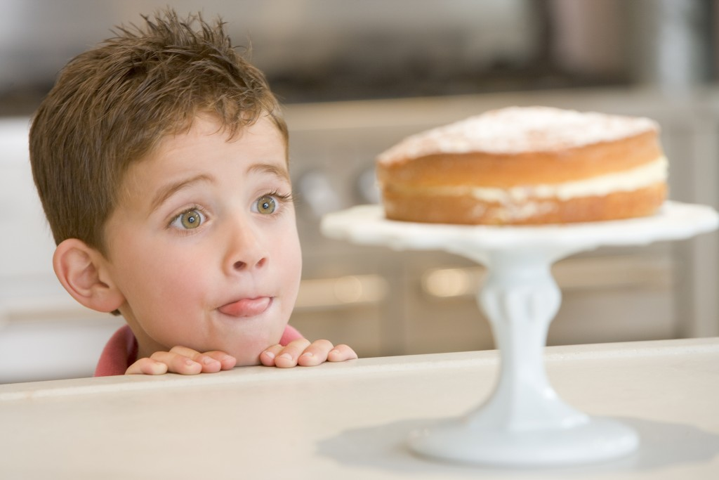 Boy staring longingly at cake at home licking lips
