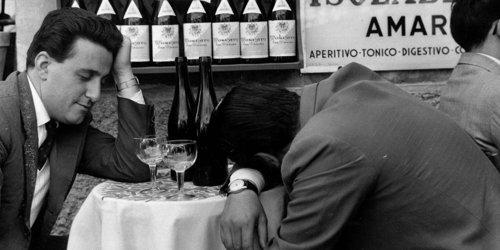 Classic Collection, Page 86, 10404106, Frascati, Italy, 23rd November 1957, Two men sit at a table, one with his head slumped on the table and the other practically asleep, with two empty bottles of wine in front of them (Photo by Popperfoto/Getty Images)